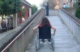 Estudiant en cadira de rodes pujant una rampa